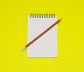 Notebook and pencil on yellow background