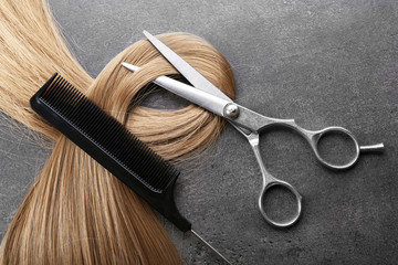 Hairdresser's scissors with comb and strand of blonde hair on grey background