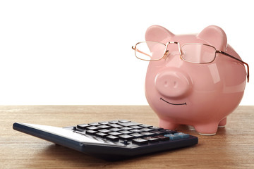 Pink piggy bank with glasses and calculator on white background