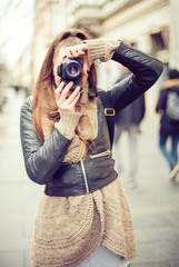 Young female photographer / Pretty young female tourist taking pictures in the city