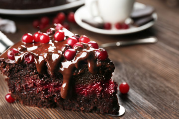 Piece of chocolate cake with cranberries on shovel and cup of tea on wooden table, closeup
