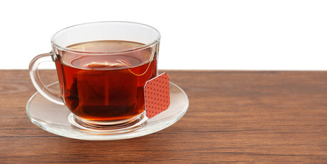 Glass cup with tea bag on wooden table over white background