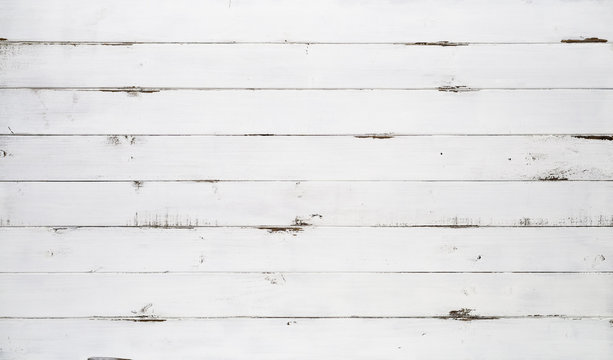 Distressed white wood texture background viewed from above. The wooden planks are stacked horizontally and have a worn look. This surface would be great as design element for a wall, floor, table etc…