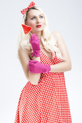 Pinup Caucasian Blond Woman With Red Sweet Candy.Posing Against White