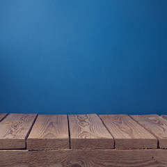 Empty wooden old table over blue wallpaper background