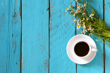 top view image of daisy flowers next to cup of coffee on blue wooden table