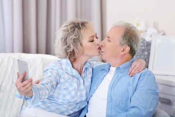 Happy mature couple kissing and taking photo of their self with mobile phone at home