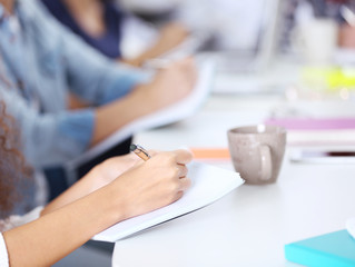 Young woman making notes at the office meeting