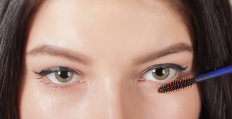 woman paints the eyelashes mascara