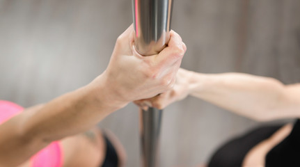 Hands on dancing pole during pole fitness class