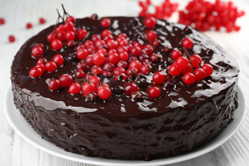 Chocolate cake with cranberries on white wooden table, closeup