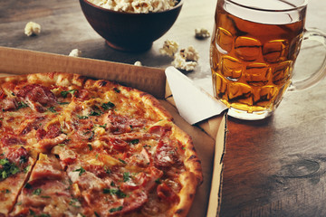 Tasty pizza in carton and glass of beer are on wooden table, close up