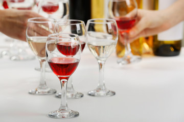 Glasses with different kind of wine and human hands holding wineglasses in the background