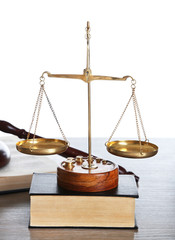 Justice scales with wooden gavel and books on white background, close up