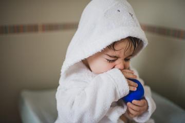 Boy sitting with bathrobe after bathing
