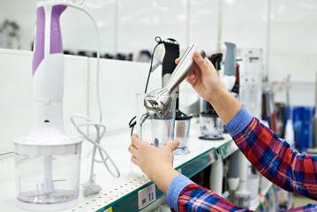 Woman chooses blender in store