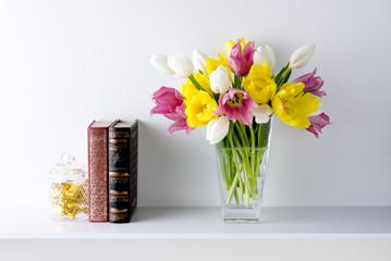 白い背景と棚と花瓶と3色のチューリップと本とお菓子
