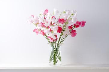 白い背景と棚と花瓶とスイートピー