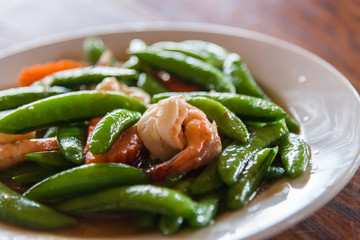 Shrimp stir and fried and green peas on white plate with selective focus