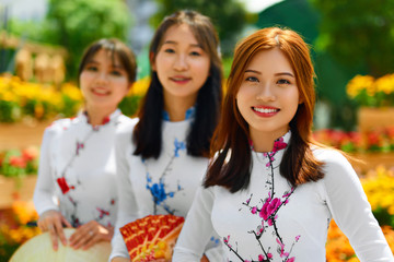 Asian People. Beautiful Happy Smiling Women ( Girls, Friends ) Wearing National Traditional Ao Dai Dresses ( Vietnamese Costume, Clothing ) In Flower Garden, Ho Chi Minh City, Vietnam. Culture Of Asia