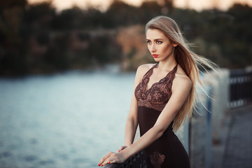Beautiful young fashionable woman posing in dress at the river coast in the evening after sunset. Vogue style. Urban background