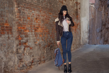 Outdoor lifestyle portrait of pretty young girl, wearing in hipster swag grunge style on urban background. Wearing hat and jeans with backpack. Spring fashion woman. Toned style instagram filters.