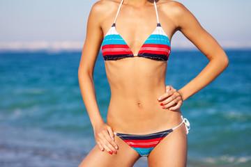 Sexy beautiful woman in creative swimwear at the sea coast. Close up body, body shot.