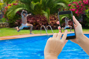 making photo of boy jumping in pool