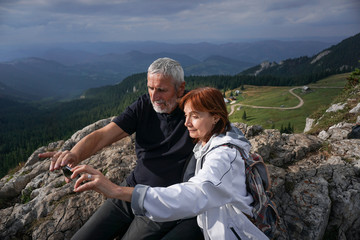 Elderly couple taking a selfie on top of a mountain