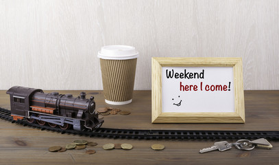 Train on railway, coffecup, money, keys and frame with text -  W