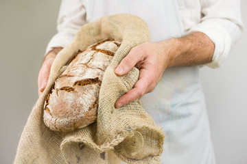 Freshly baked bread from the baker. Baker holding fresh bread in the hands. Rustic style.