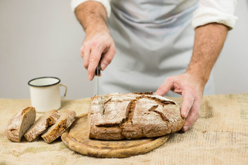 Male cook cuts bread. Rustic style.