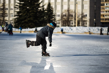 cute little boy learning to skate in sunny spring day