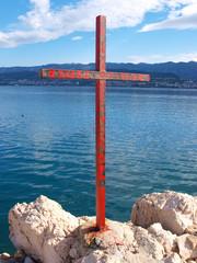 christian iron cross on sea coast