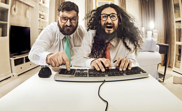 Two nerdy guys working with a computer