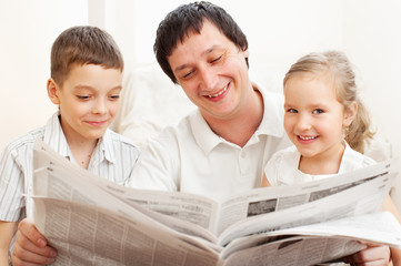 Family reading a newspaper