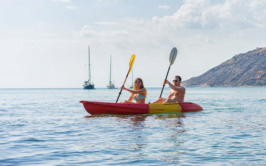 Couple exploring calm tropical bay by kayak.