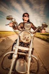Fototapete - Biker girl on a motorcycle