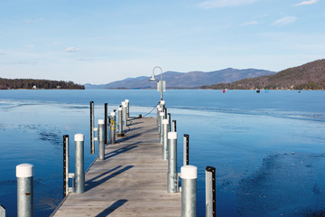 Color DSLR stock image of a frozen Lake George, with a dock in the foreground and Adirondack Mountains in background. Horizontal with copy space for text