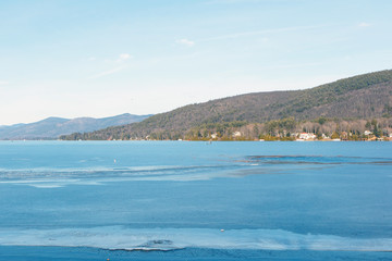 Color DSLR stock image of a frozen Lake George, with lake houses on the shore and  Adirondack Mountains in background. Horizontal with copy space for text