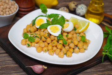 Mediterranean cuisine. Dish of chickpeas with mint, olive oil and lemon sauce on a wooden background