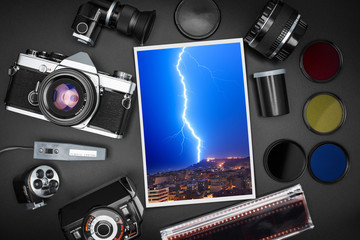 Analog SLR camera equipment around a printed photo of a lightning that strikes over the city