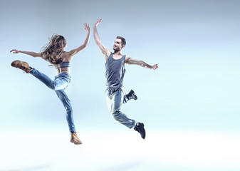 Two young dancers in a jumping pose
