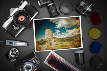 Analog SLR camera equipment around a printed photo of a Sardinian landscape with ancient Spanish wachtower in spring