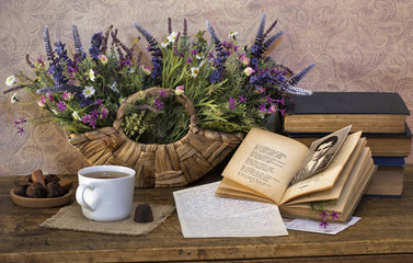 Still life with bright dried flowers, old books, glass in cup ho