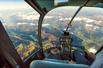 Wall Murals Helicopter Helicopter cockpit flying on mountain landscape and cloudy sky, with pilot arm driving in cabin. Spectacular aerial view of Alps mountain chain.