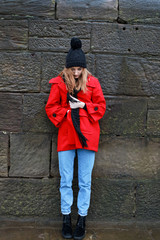 Woman in red jacket leaning against a stone wall in the rain and
