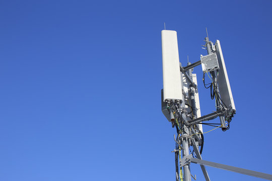 panel antenna mobile communication on background blue sky. telecommunications antenna tripod on the tower. cellular communications 2g, 3g, GSM, LTE. bottom view. copy space for your text