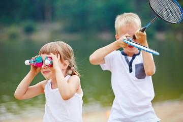 Kinder spielen mit Federball und Schläger