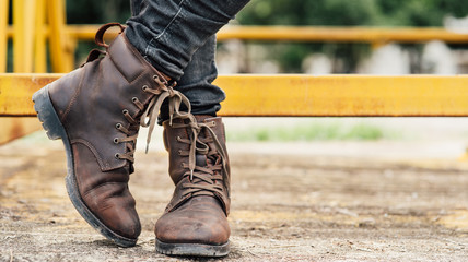 Men fashion legs in black jeans and brown leather boots